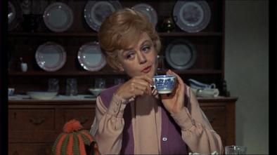 Miss Price, une tasse de thé à la main