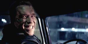 Arnold Schwarzenegger au volant d'un camion, se retourne en souriant de toutes ses dents.