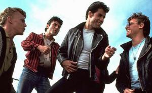 John Travolta dans le rôle de Danny Zucko, qui rit bien avec ses amis.