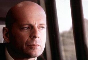Bruce Willis regardant par la fenêtre du train.