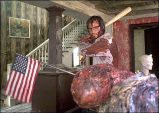 Le papa, brandissant une batte de baseball pour achever un mutant ayant un drapeau américain planté dans le crâne.
