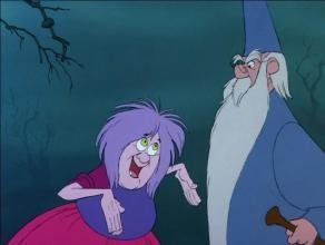 Madame Mim et Merlin, Mim semble faire allusion à la taille de quelque chose avec ses mains.