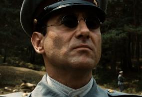 Le capitaine Vidal portant de petites lunettes de soleil rondes.