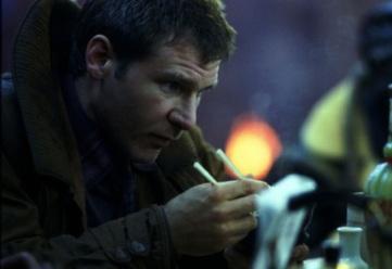 Deckard mangeant des nouilles dans la rue, sous la pluie.