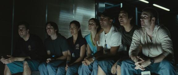 Les personnages, assis en ligne et souriant à la vue de la planète Mercure.