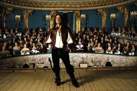 Romain Duris dans le rôle de Molière, debout sur scène et regardant la caméra avec détermination.
