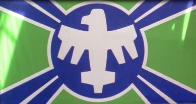 Le drapeau de la Federation : un aigle blanc dans un cercle bleu dont partent quatre branches bleues, le tout sur fond vert.