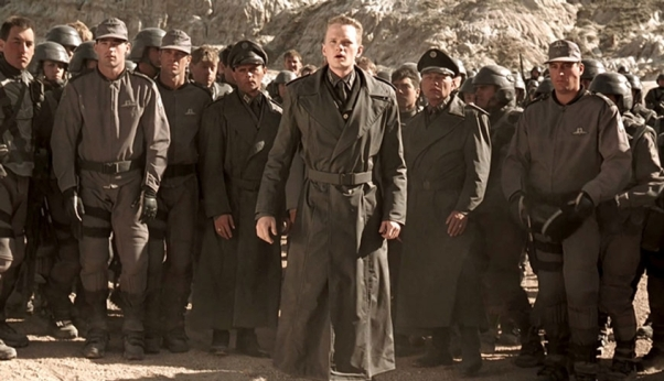 Carl Jenkins entouré de soldats, tous en uniformes d'inspiration nazi.