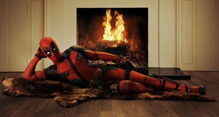 Deadpool étendu sur une peau de bête devant un feu de cheminée.