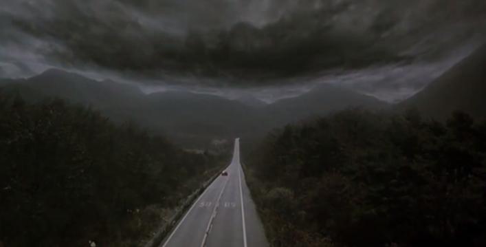 Le plan final du film où une voiture file sur une route vers un horizon nuageux.