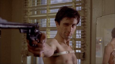 Travis jouant avec ses revolver devant le miroir.