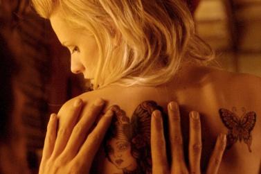 Elise de dos se retournant en sentant les mains de Didier contre elle.