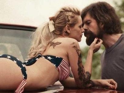 Elise, vétue d'un bikini aux couleurs des USA symbolisant le rêve de Didier, étendue sur son pick-up et sur le point de l'embrasser.