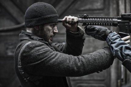 Chris Evans braquant un fusil sur son front.