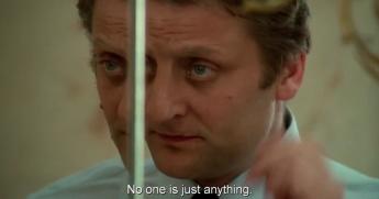 """Bruno Cremer, incarnant l'homme d'affaires français, en train de se préparer devant un miroir. Le sous-titre de la conversation dit que """"no one is just anything"""", traduction du dialogue """"personne n'est quelque chose et rien de plus""""."""