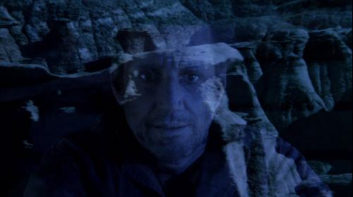 Le visage déformé par la terreur et la fatigue de Roy Scheider mélangé en transparant avec le paysage désertique qui entoure le dernier camion.