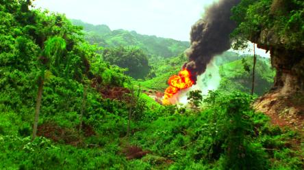 L'incendie du puits de pétrole dont les flammes orangées se détachent de la vallée verdoyante dans laquelle elle a lieu.