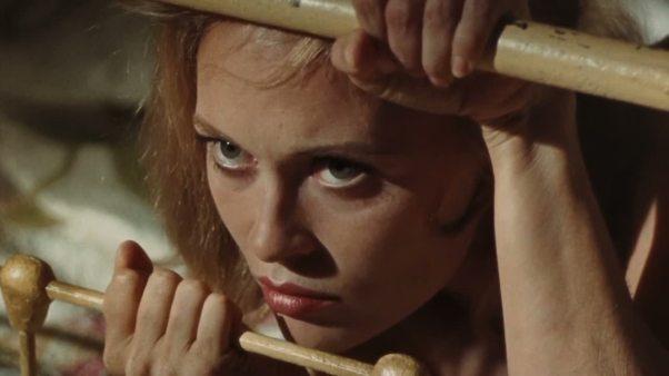 Faye Dunaway, filmée en gros plan à travers les barreaux de son lit.