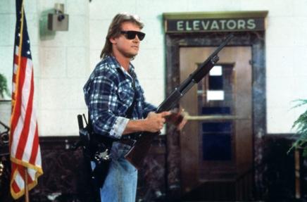 John Nada, fusil à la main, devant la porte d'un ascenseur fermée