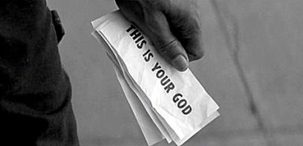 """Un homme tenant une liasse de papiers sur lesquels est écrit """"ceci est ton Dieu"""", les papiers étant à l'origine des dollars."""