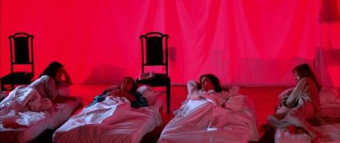 Suzy et ses camarades dormant ensemble dans une salle commune.