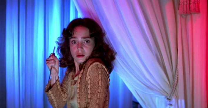 Suzy, un couteau à la main, se glissant entre des draps éclairés de rouge et de bleu