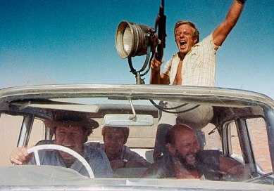 Les personnages de Wake in Fright, fusils en main et à bord d'une voiture, pourchassant des kangourous à grande vitesse dans le désert