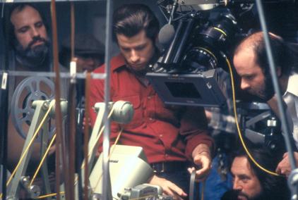 Brian de Palma, John Travolta et une partie de l'équipe du film regardant le rendu d'un plan.