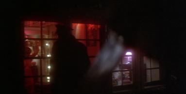 La scène d'ouverture de Blow Out avec en premier plan un couteau levé pointant directement vers un policier qui tourne le dos à la caméra et qui regarde par la fenêtre d'un dortoire