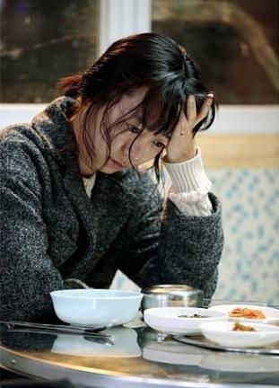 Bae Doona, l'actrice incarnant la femme du malheureux héros, assise seule à table devant sa nourriture.