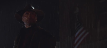 Clint Eastwood sous la pluie, un drapeau américain derrière lui.