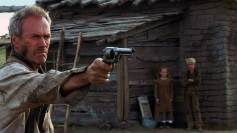 Clint Eastwood pointant son arme vers le bord droit de l'écran. Au fond, visibles sous son bras tendu, ses deux enfants le regardent.