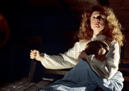 Mrs. White s'apprêtant à poignarder Carrie dans le dos.