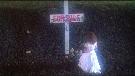 """Sue devant le panneau """"A vendre"""" de ce qu'était la maison de Carrie."""